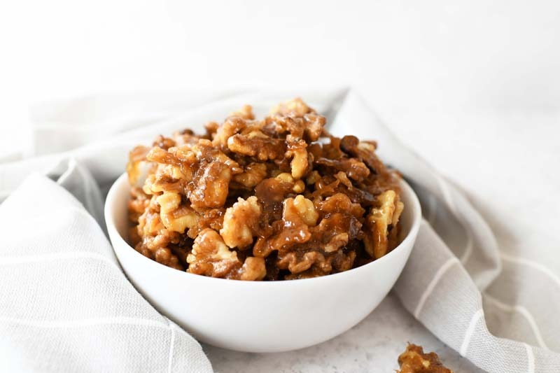 Candied Walnut Recipe on a white table. There is a grey, striped napkin on the table.