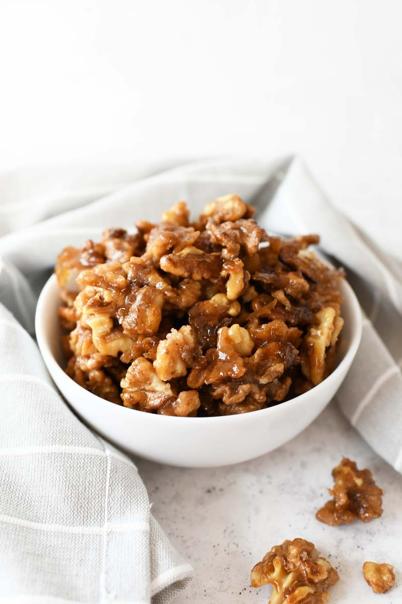 Candied Walnuts in a white bowl with a grey, striped napkin.