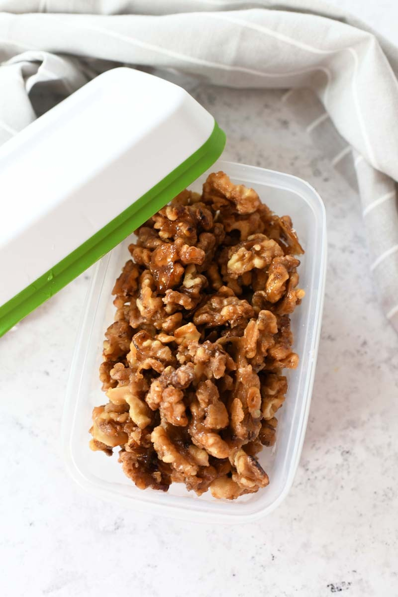 Candied Walnuts in a green and white plastic container on a grey table with a grey napkin.