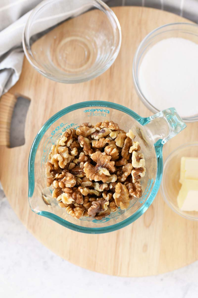 Candied Walnuts ingredients in glass containers on a wooden trivet.