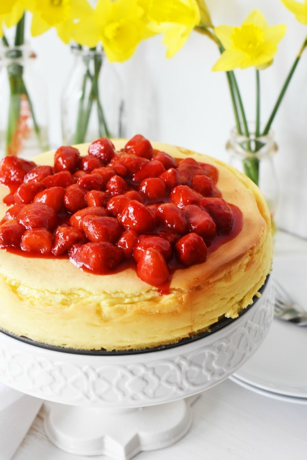 Crustless cheesecake  topped with strawberries on a white cake stand.