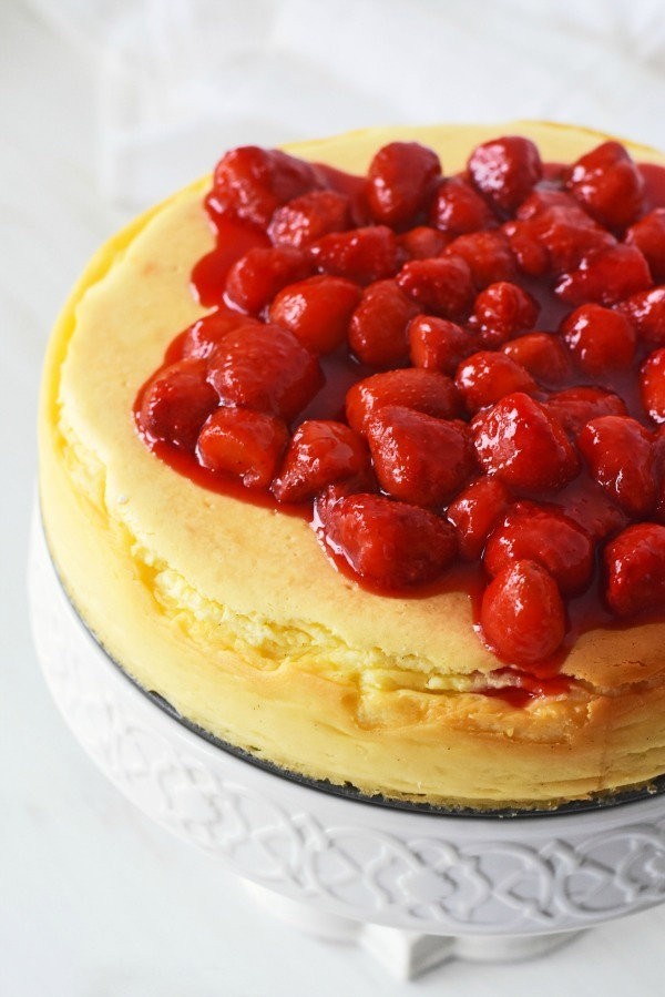 crustless cheesecake topped with strawberries on a white cake stand