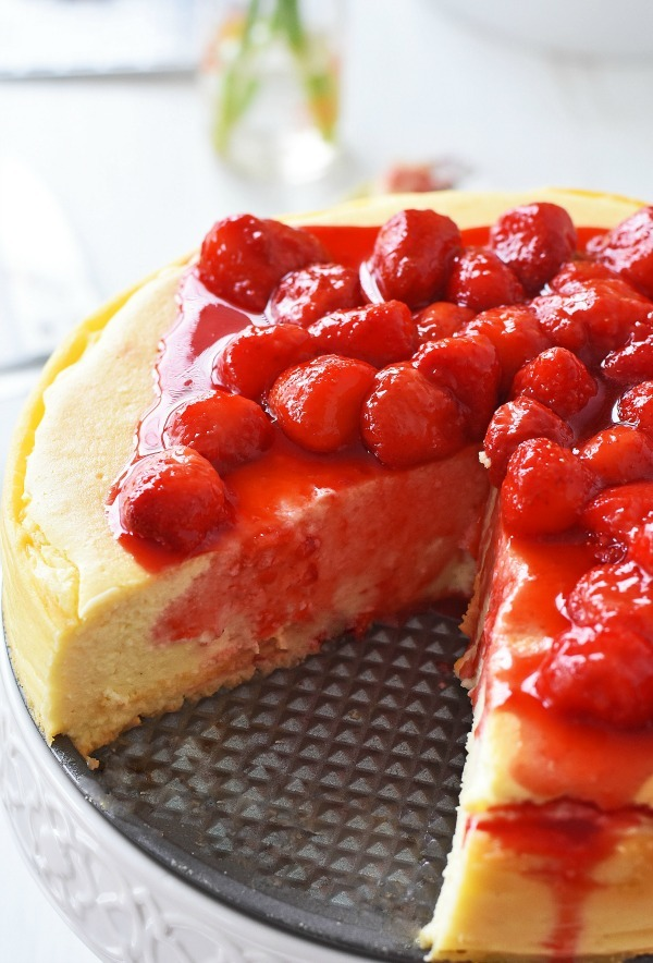 Strawberry Topped Crustless Cheesecake with 1 slice removed on a cake stand