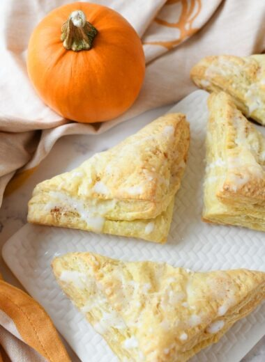Pumpkin Puff Pastries on a white plate with a real pumpkin.