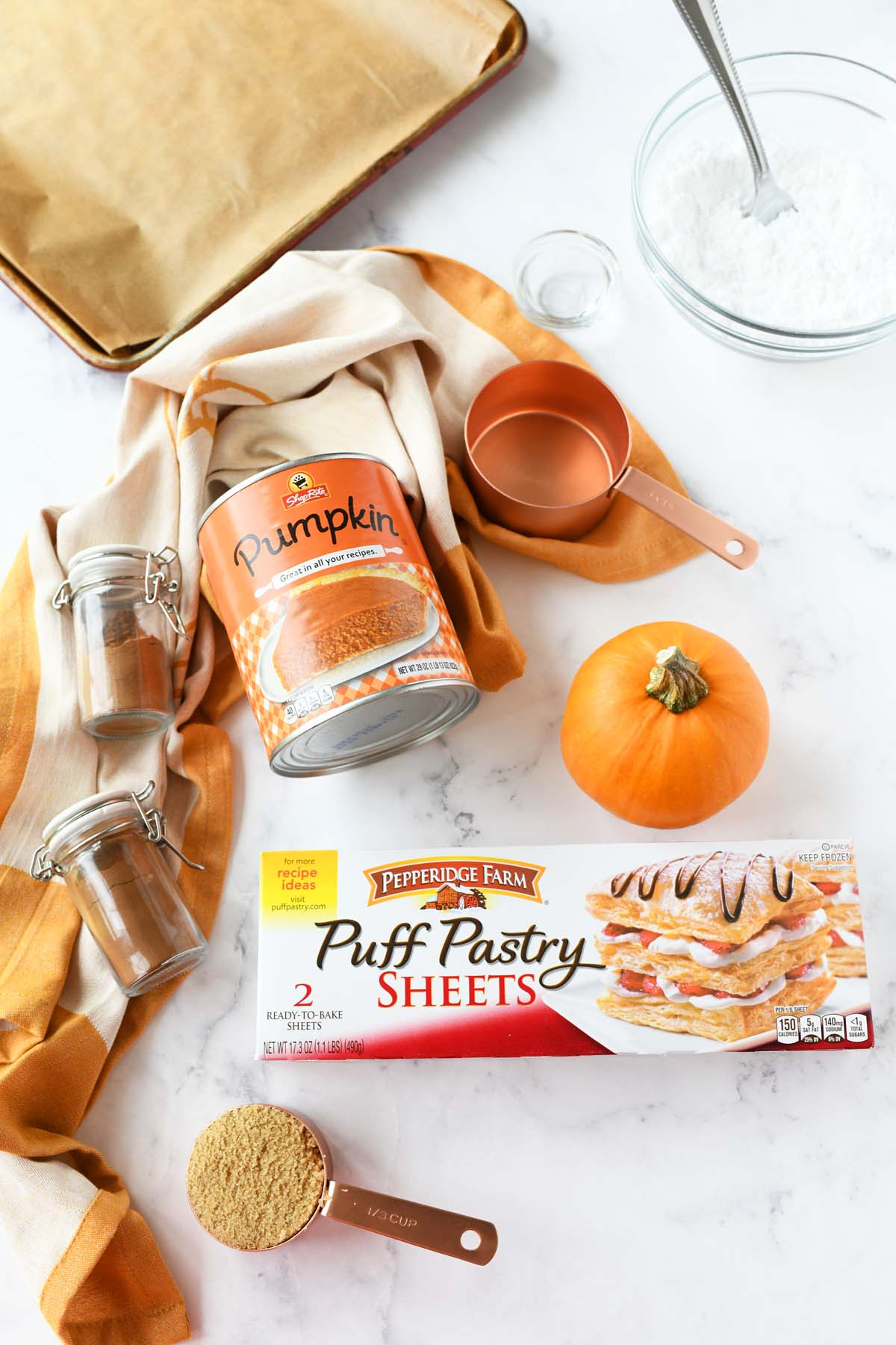 Pumpkin puff pastry ingredients on a white table.