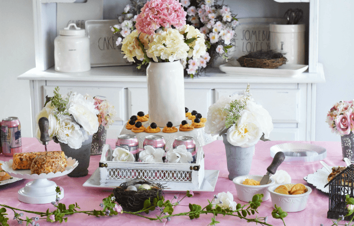 Welcome to Spring Floral Tablescape & Cheese Appetizer Ideas- Get inspired with this floral spring tablescape that features white and pastel pink color themes. See what cake stands, trays, and vases come together to make this silk flower spread. Also, get inspired with some easy cheese-themed appetizers to serve.