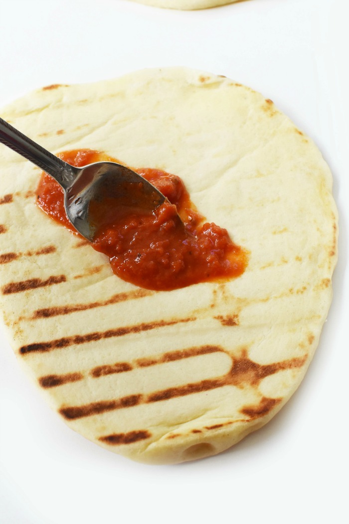 Adding sauce to grilled flatbread 1