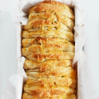 Garlic and Cheese Pull Apart Biscuit Bread in a pan with parchment paper