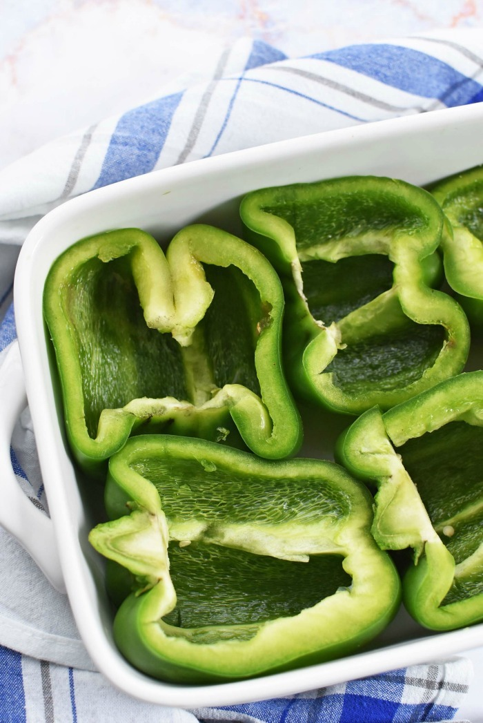 Halved green bell peppers in pan