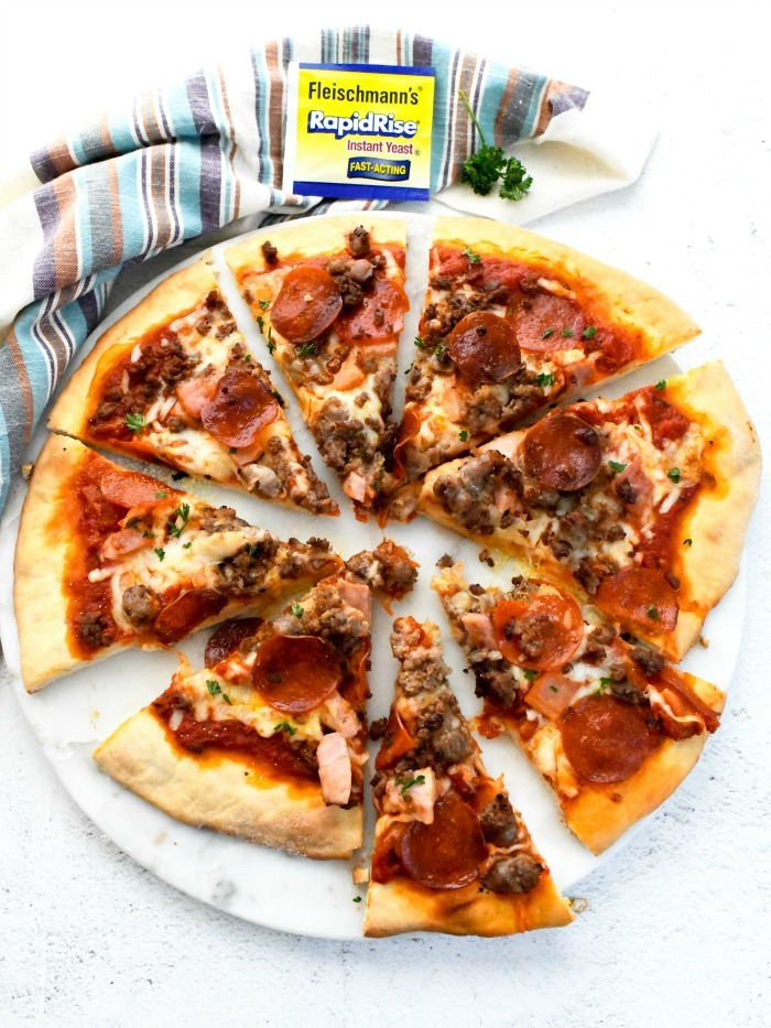 Meat Pizza Recipe on white table with striped napkin