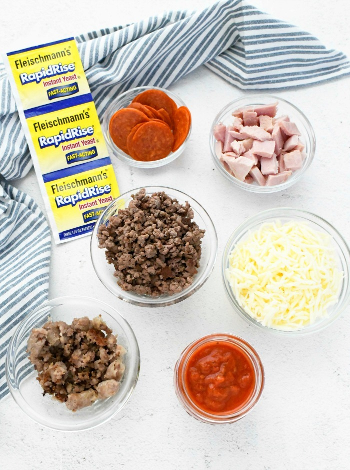 Meat lovers Pizza Recipe ingredients on a white table with a striped towel