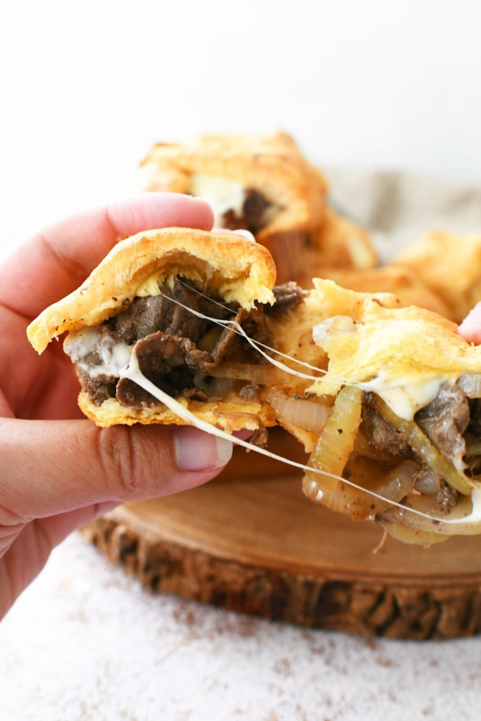 Hand grabbing Cheesy Steak bombs with cheese pull.