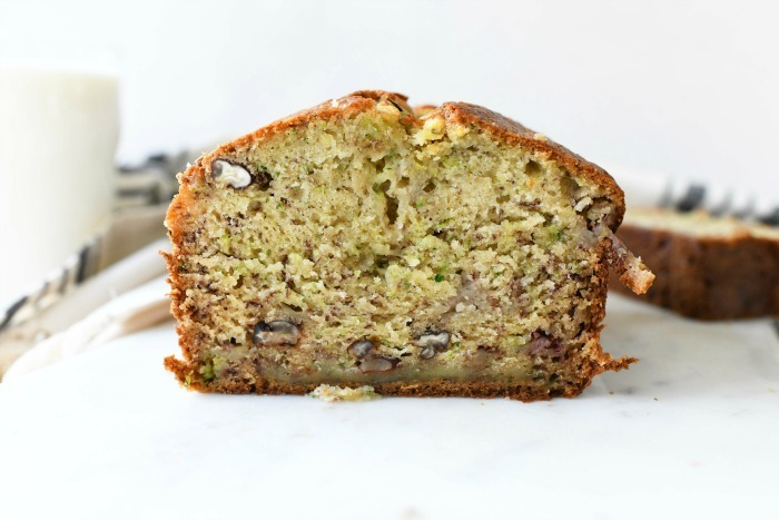 Banana bread with zucchini slice horizontal on white surface with milk in background.