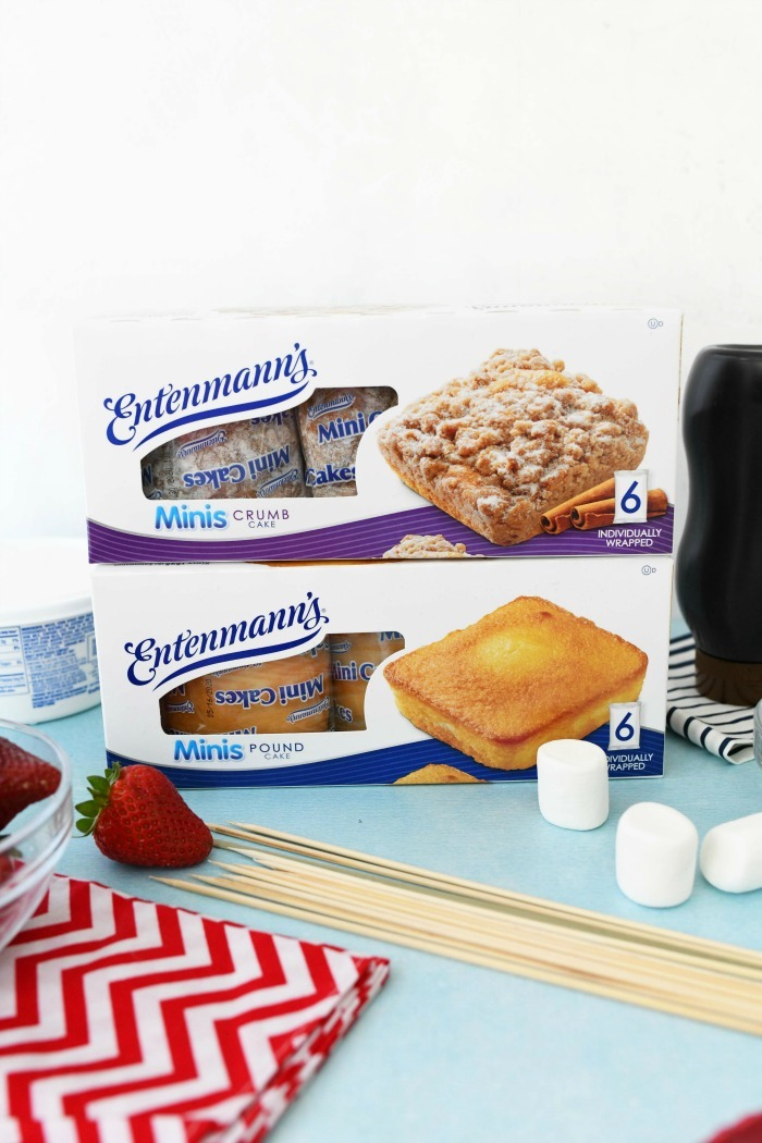 Entenmanns Minis boxes on blue surface with berries and kabob supplies.