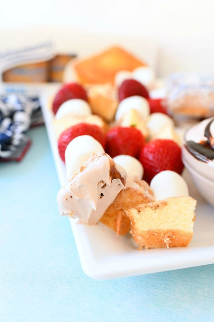 Fruit and cake Kabobs with fluff dip on them.