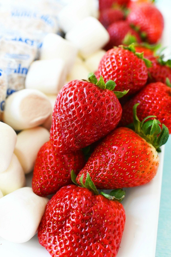 Jumbo red strawberries and marshmallows on white plate.