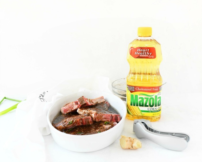 Mazola corn oil bottle with marinated pork chops.