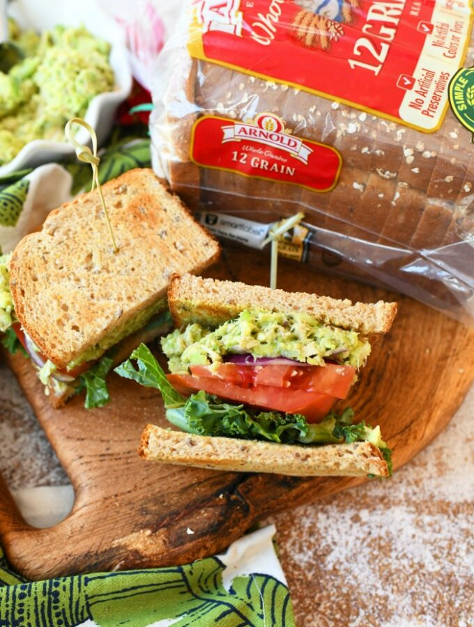 Tuna salad made with avocado halved with a toothpick on a wooden serving board near a bag of Arnold bread.