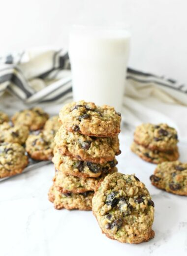 Zucchini Oatmeal Cookies on marble table with white glass of milk.
