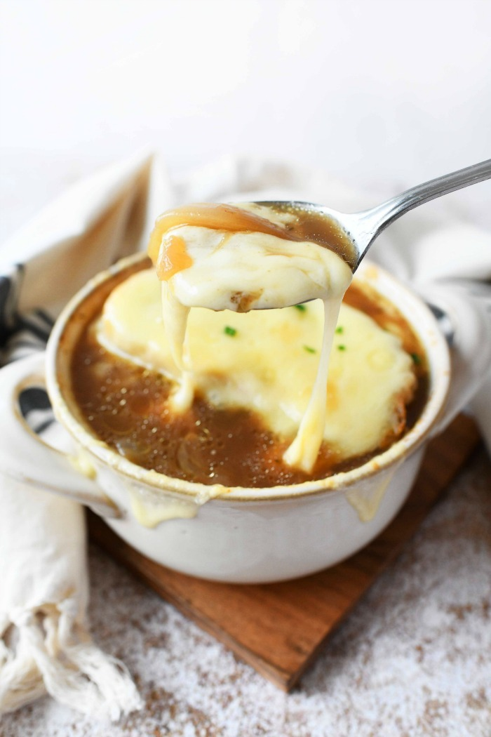 Cheesy French Onion Soup in silver spoon.