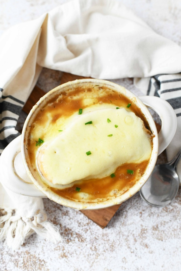 Homemade French Onion soup on table with spoon and napkin.