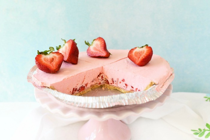 No-Bake Strawberry pie on a pink platter with a blue background.