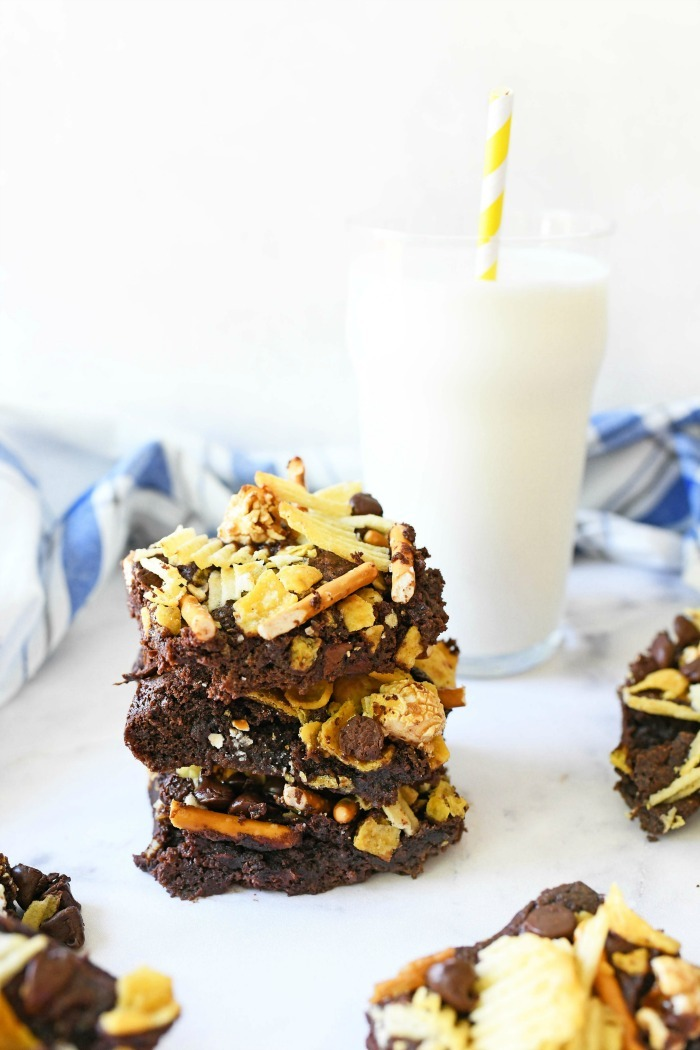 Junk food brownies stacked on white marble table with a glass of milk.