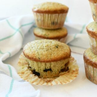 Bakery style zucchini muffins stacked on a white table.