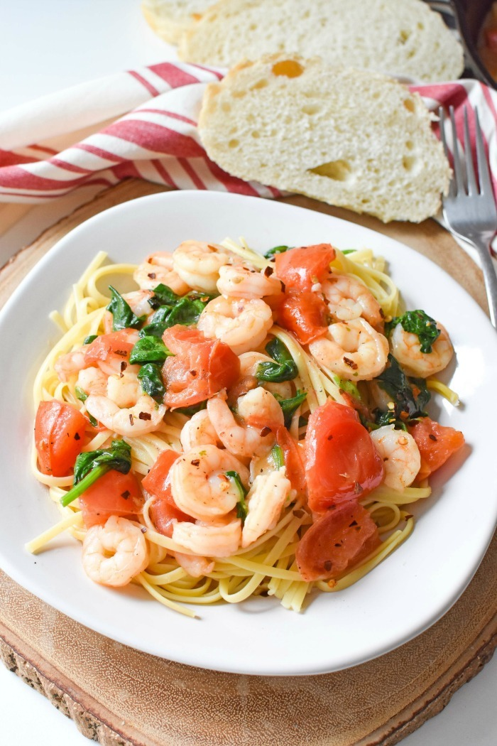 Easy Shrimp Scampi in a white dish with bread.