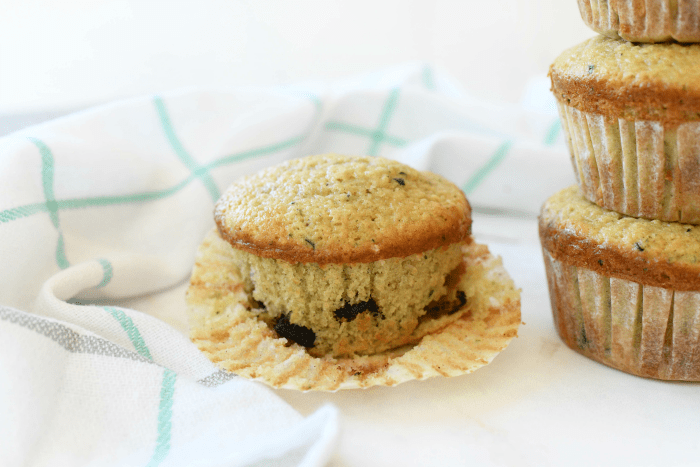 Jumbo Zucchini Muffins on a white table with one unwrapped.