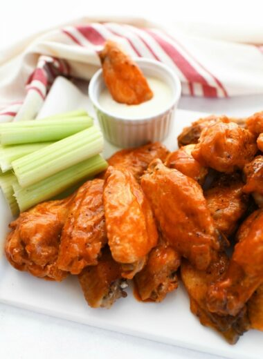Oven-Baked Buffalo chicken wings with ranch on a white table.