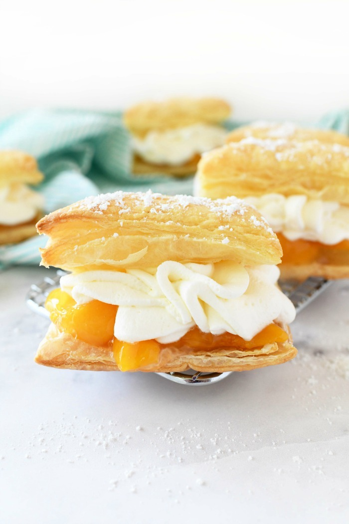 Peaches & cream puffs on wire rack with blue napkin.