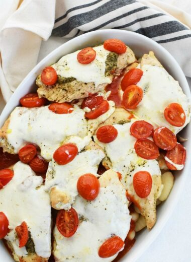 Pesto Baked Chicken with Mozzarella in an oval dish on a white table with striped napkin.