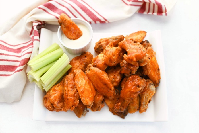 baked buffalo chicken on a white rectangle plate with celery and ranch.
