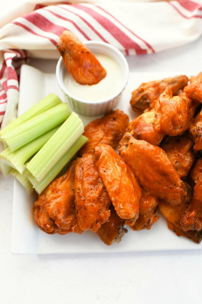crispy oven baked wings dipped in ranch with a white and red napkin.