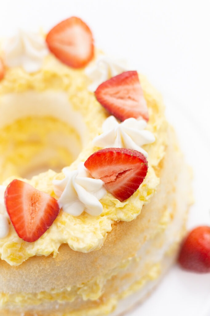 angel food cake with pineapple and berries on white table.