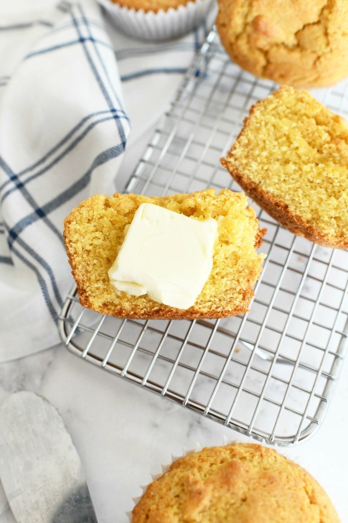 Corn muffins with butter on a baking rack.