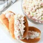 Deli Style Seafood Salad finger rolls on a white platter.