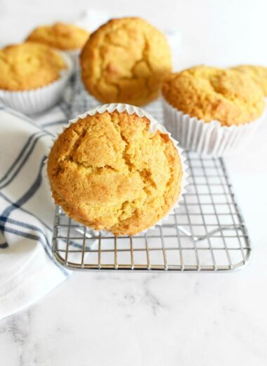 Jumbo corn muffins on a silver baking rack.