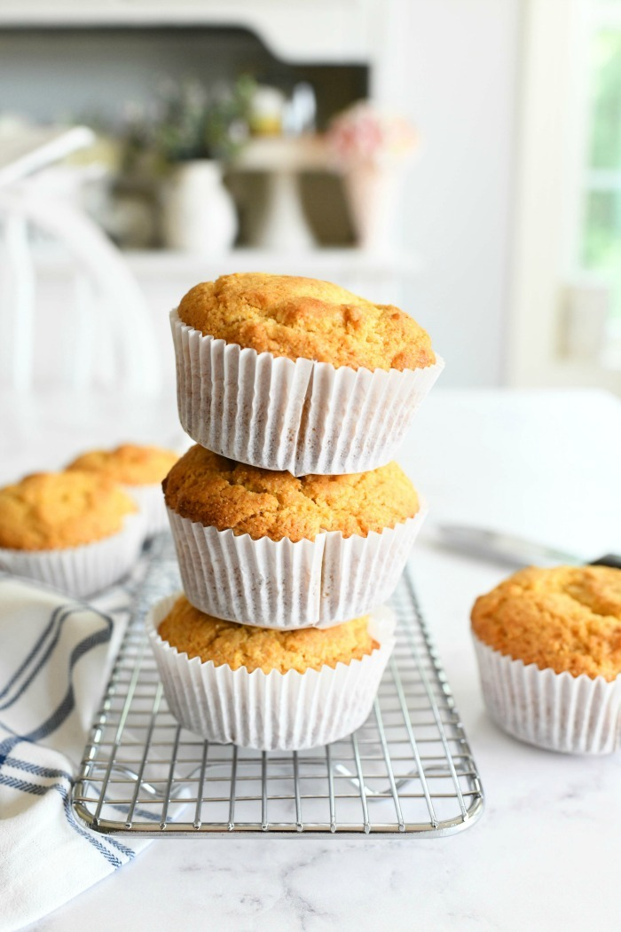 Jumbo corn muffins stacked on a table.