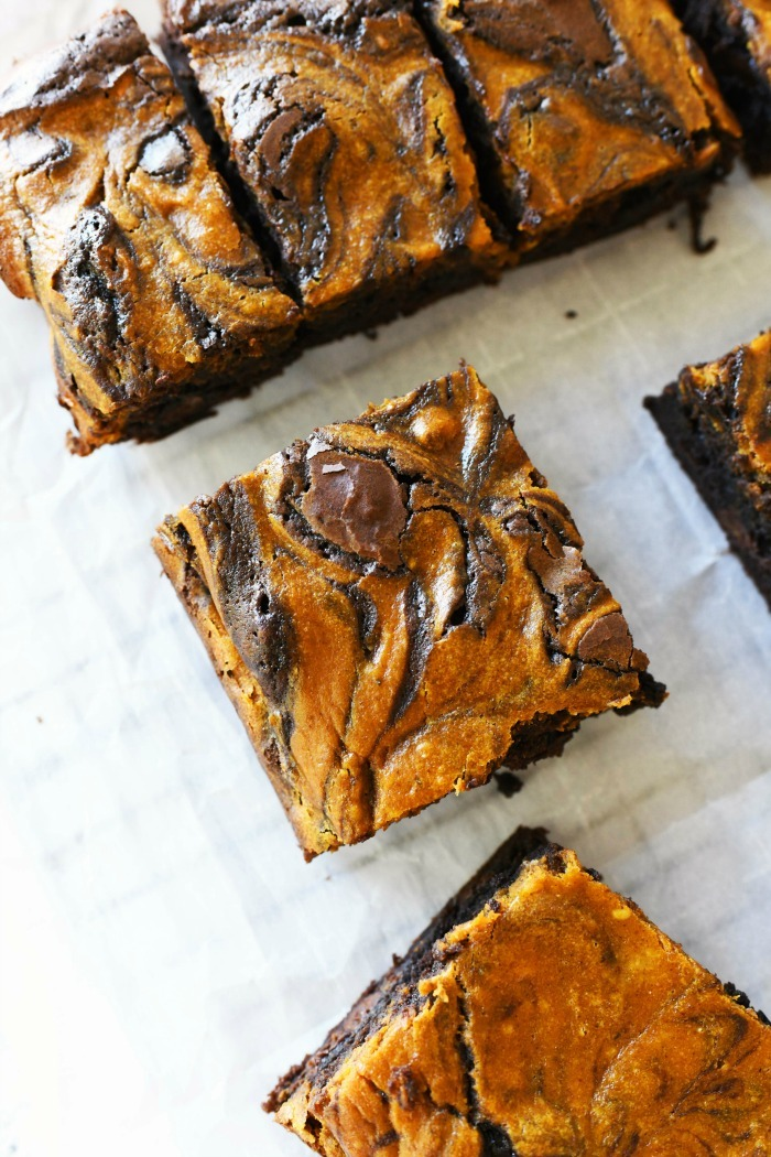 Pumpkin swirl brownies cut into squares on a white table.