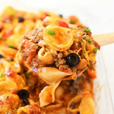 Taco Pasta Casserole in a glass dish with a wooden spoon.