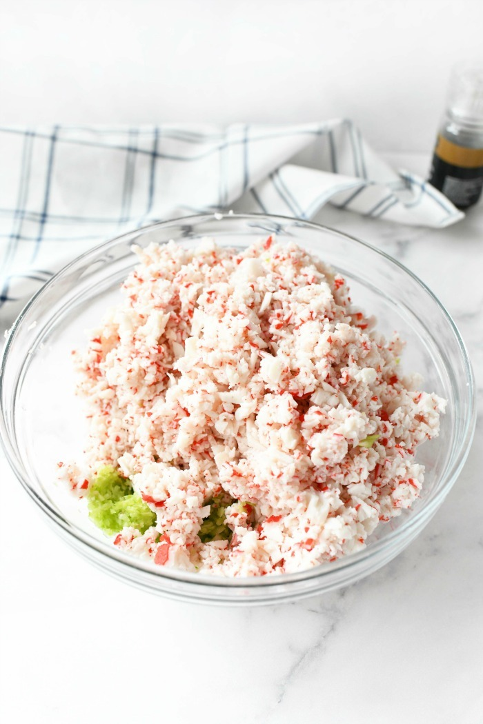 seafood salad with celery in a glass dish on a white table.