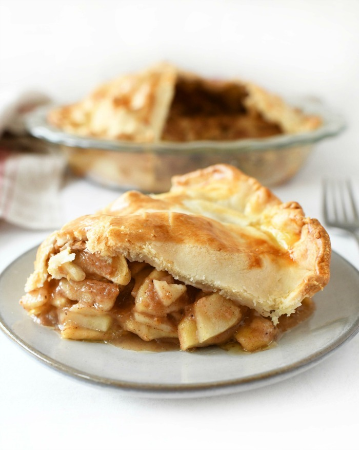 Apple Pie with store bought crust sliced on a plate with a fork.
