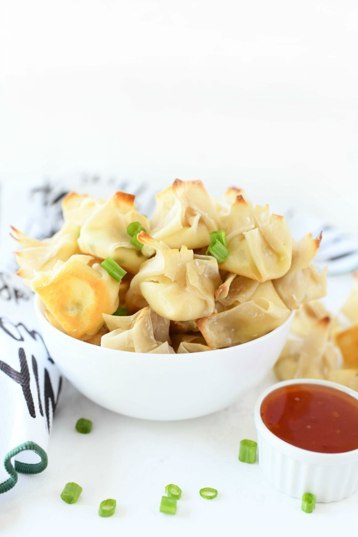 Baked cream cheese wontons in a white bowl with chili dipping sauce in a white cup.