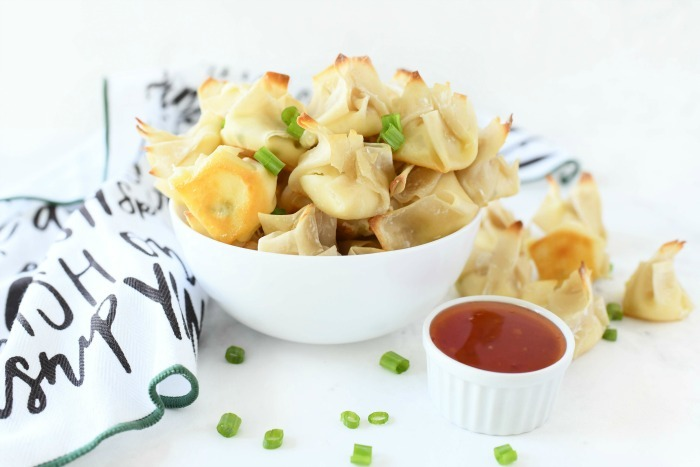 Baked wontons with cream cheese on a white table with a napkin and chili sauce.