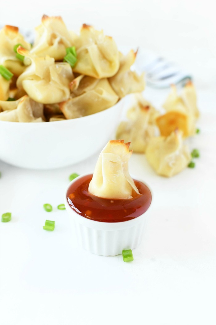 Cream cheese wonton in sweet chili sauce in a chili dipping cup.