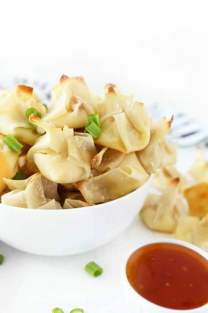 Cream cheese wontons in a white bowl with chili sauce.