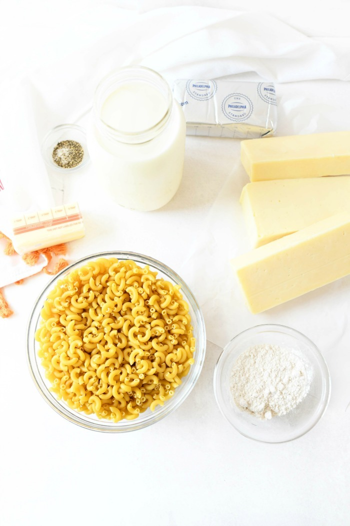 Creamy macaroni and cheese ingredients on a white table.