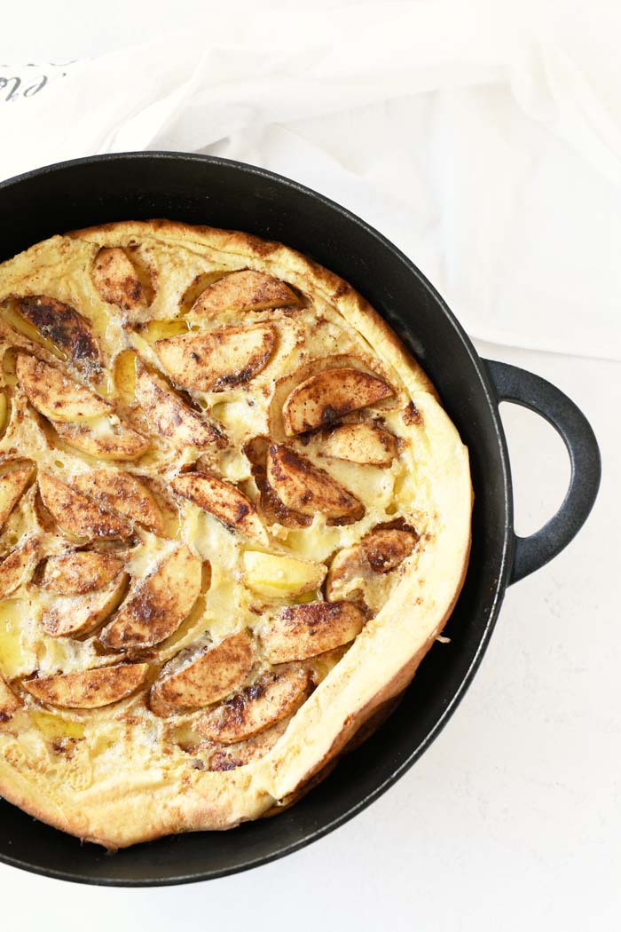 German Apple Pancake baked up bubbly and golden brown in a black cast iron skillet.